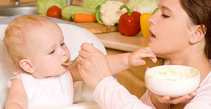 Мама кормит кашей малыша