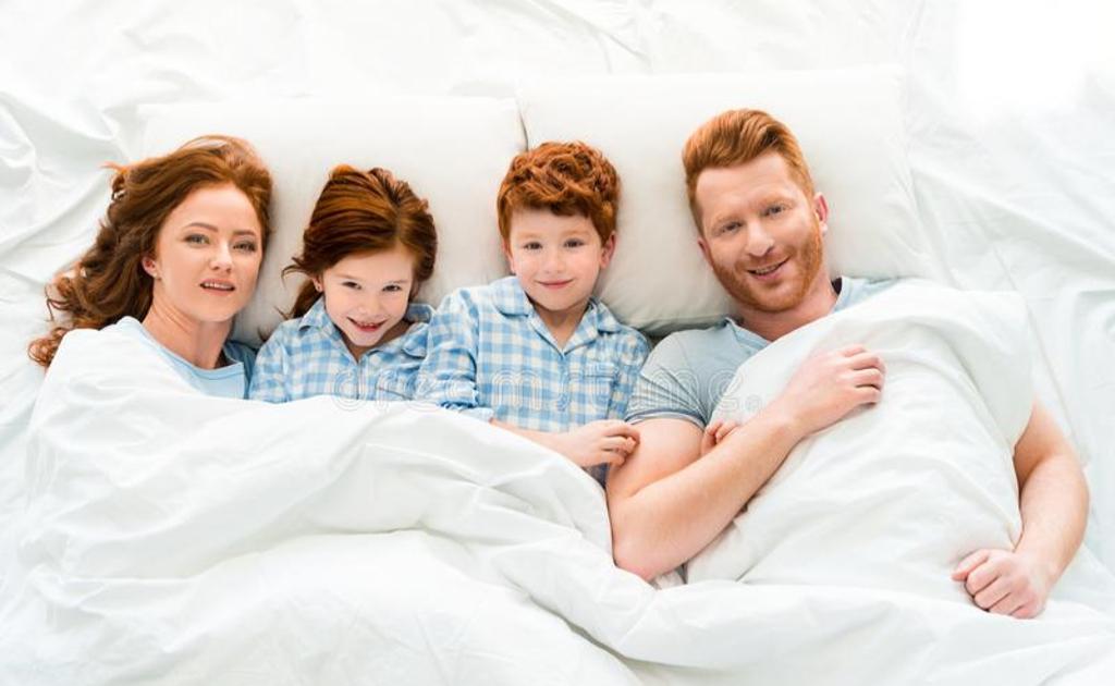 Счастливая семья в пижамах лежит в постели