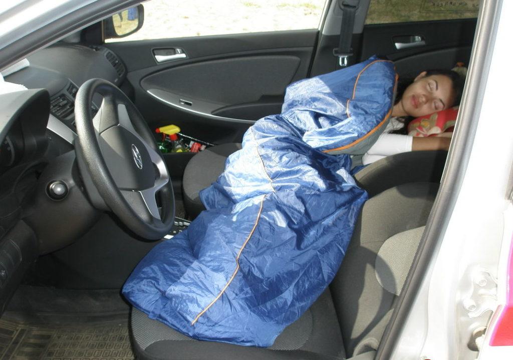 Женщина спит в машине в спальном мешке